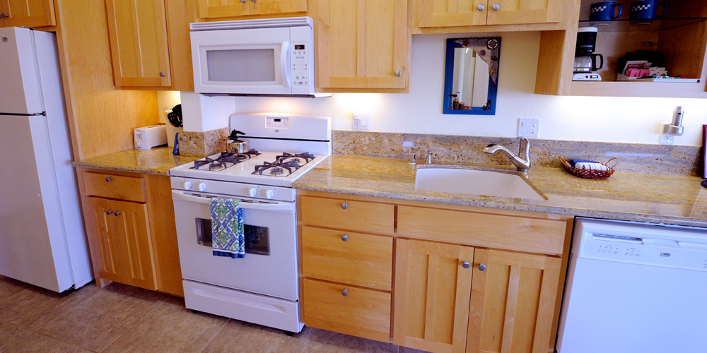 Kitchen features gas stove, new appliances and granite slab countertops